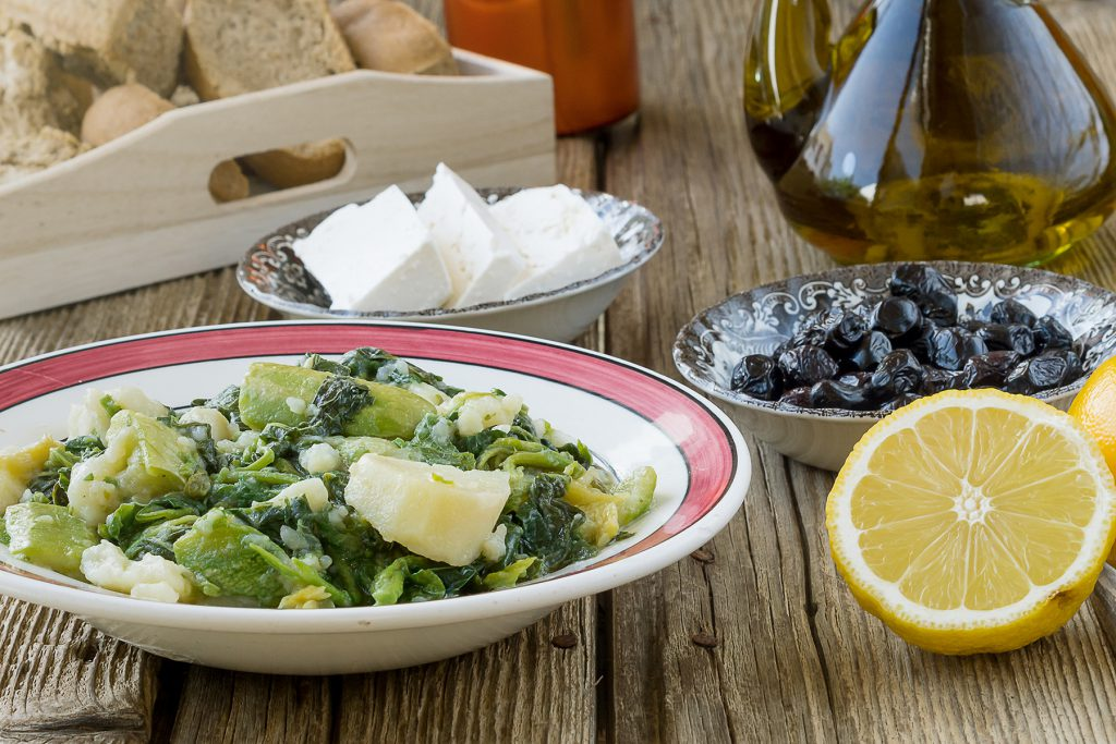dishes of wild greens, feta cheese and olive oils
